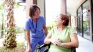 Ältere Krankenschwester Gespräch mit Patienten im Rollstuhl außerhalb hospital