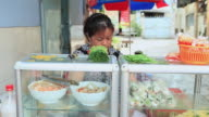 MS Mature Vietnamese woman cooking in stand of  summer rolls / Quan Binh Thanh, Ho Chi Minh, Vietnam