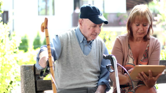 Mature Woman and Senior Man Using Digital Tablet