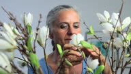 Mature woman arranging and smelling flowers