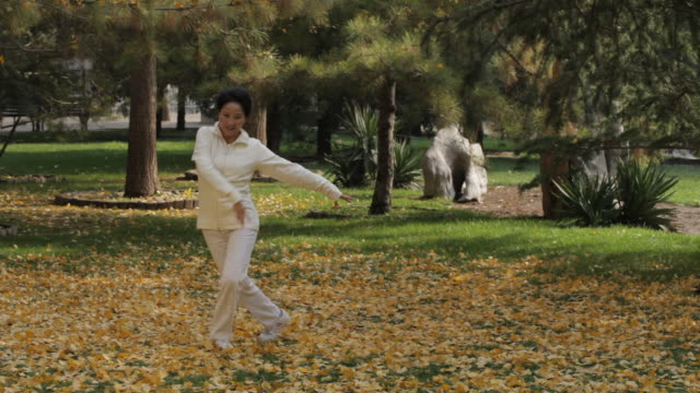 WS Mature woman dancing on fallen leaves in park / China