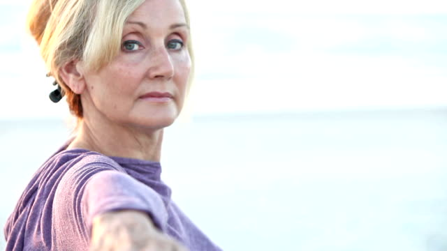 Mature woman doing yoga, staring with hand stretched out