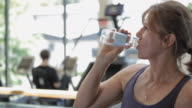 MS PAN Mature woman drinking water from bottle in gym / Vancouver, British Columbia, Canada