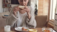 Mature woman enjoying in breakfast at home and showing OK sign while looking at camera.