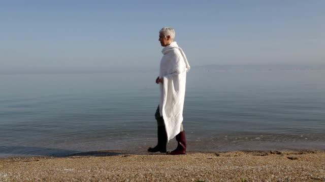 Mature woman enjoys a walk on the beach by the sea