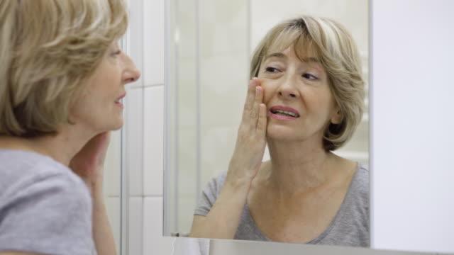 Rijpe vrouw haar gezicht in de spiegel onderzoeken