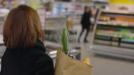 Mature woman grocery with paper bag in supermarket