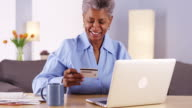 Mature woman happily paying her bills