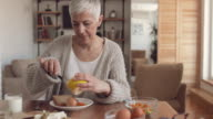 Mature woman having breakfast and spreading butter on a slice of bread.
