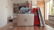 Mature woman having video chat with someone and showing new clothing she has bought.