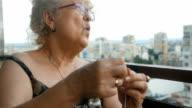 Mature woman knitting on a city balcony