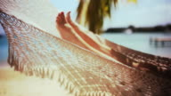 MS Mature woman lying in hammock on beach / English Harbor, Antigua and Barbuda