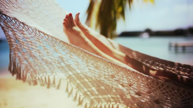 MS Mature woman lying in hammock on beach / English Harbor, Antigua and Barbuda