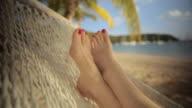 CU Mature woman lying in hammock on beach / English Harbor, Antigua and Barbuda