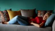 Mature woman lying on sofa and feeling pelvic pain