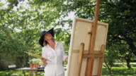 MS Mature woman painting in garden / London, United Kingdom