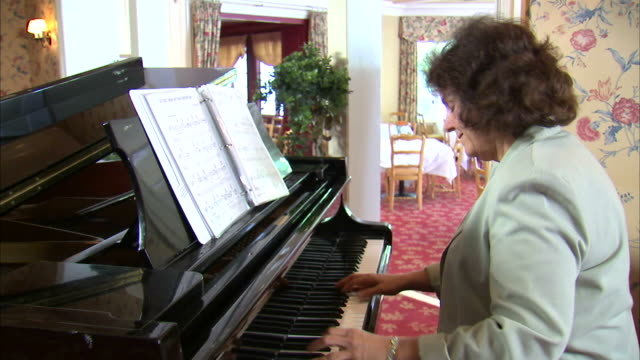 MS DS Mature woman playing piano / Salt Lake City, Utah, USA