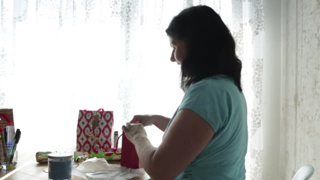 MS Mature woman putting gift in bag for Christmas.