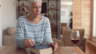 Mature woman reading a book at home and enjoying in a glass of wine.