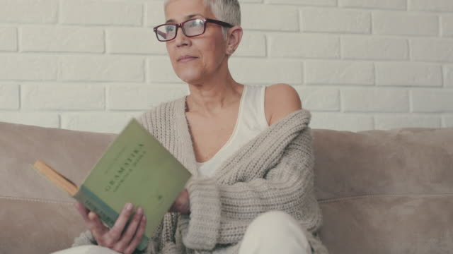 Mature woman reading a novel while relaxing on the sofa.