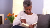 Mature woman reading book on couch