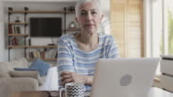 Mature woman reading something from the Internet on her laptop at home.