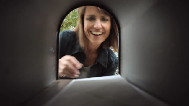 MS Mature woman retrieves mail from mailbox / Neenah, Wisconsin, USA