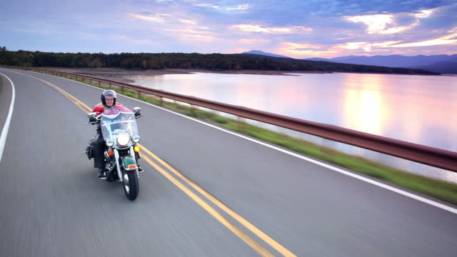 MS POV Mature woman riding motorcycles on country road with along lake and mountains at sunset / West Hurley, New York, United States