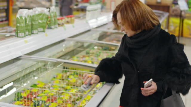 Mature woman shopping in frozen section