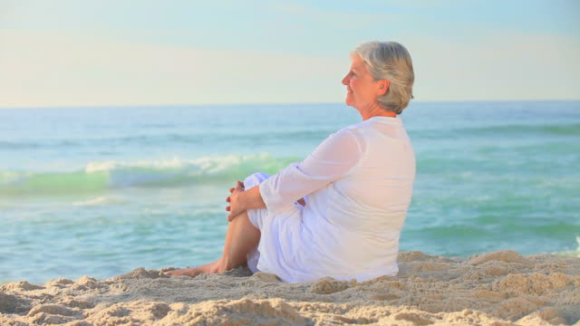 Mature woman sitting on a beach / Cape Town, Western Cape, South Africa