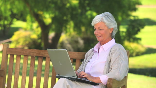 Mature woman surfing on her laptop outdoors / Cape Town, Western Cape, South Africa