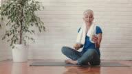 Mogen kvinna talar i mobiltelefon medan du sitter på träningsmatta efter träning.