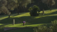 LS mature woman teeing off in last afternoon light, RED R3D 4K