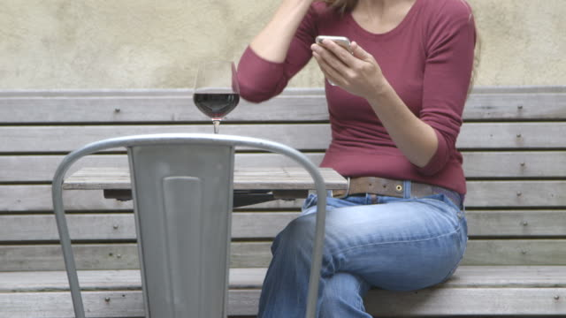 A mature woman texting at an outdoor table while enjoying a glass of wine