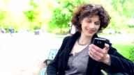 DOLLY: Mature woman texting in a park