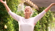 A mature woman tosses flower petals in the air.