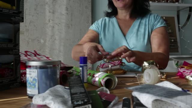 TS MS Mature woman tying ribbon on christmas gift.