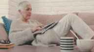 Mature woman typing e-mail on laptop and taking a nap on the sofa.