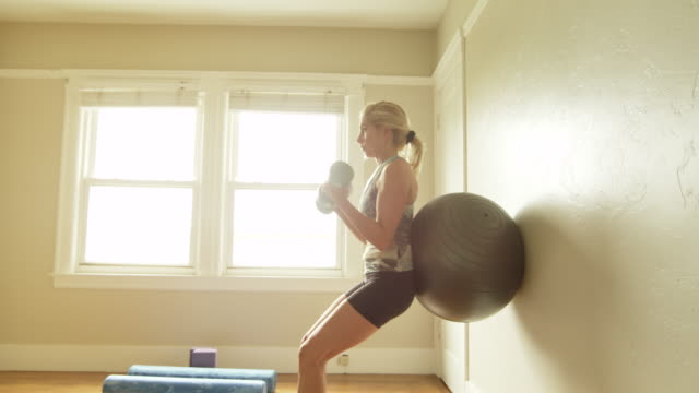 A mature woman uses an exercise ball in her home gym.