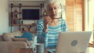 Rijpe vrouw met laptop en typen van een e-mail thuis.