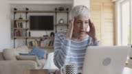 Mature woman using laptop at home and feeling frustrated about an e-mail she has received.