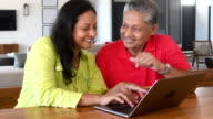 Mature woman using laptop with senior man watching and smiling