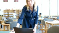 Mature woman walking into focus to study at computer in college library