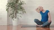 Mogen kvinna uppvärmning och stretching hennes hals medan du tränar hemma.