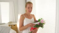 Mature woman with bouquet of flowers and a love letter