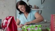 MS Mature woman wrapping christmas gifts.