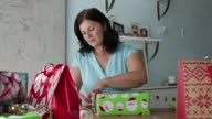 ZI MS Mature woman wrapping christmas gifts.