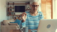 Mature woman writing e-mail on laptop and drinking coffee.
