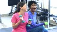 Mature women at the gym exercising, talking, laughing