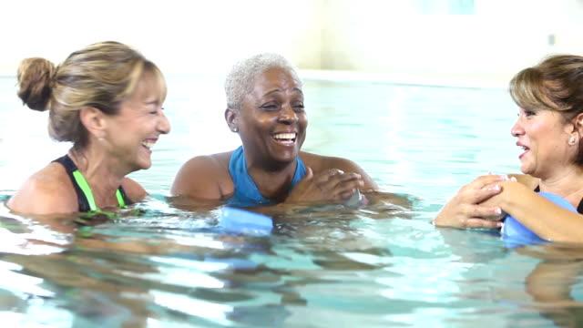 Mature women doing water aerobics, talking, laughing